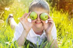 Il ragazzo biondo teenager sta tenendo le mele verdi Immagini Stock