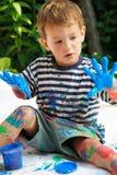 il ragazzo blu passa i suoi giovani della vernice fotografia stock