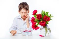 Il ragazzo in camicia bianca con le peonie ed il vaso di vetro innaffiano Fotografia Stock