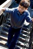 Il ragazzo cammina sul ponticello del campo da giuoco Fotografia Stock Libera da Diritti