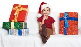 Il ragazzo in cappello rosso dell'assistente di Santa con i contenitori di regalo fa un desiderio - concetto di festa di natale Immagine Stock