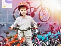Il ragazzo in casco sceglie con la bicicletta nel negozio di sport immagini stock libere da diritti