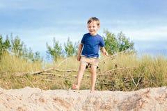 Il ragazzo caucasico del bambino che gioca sulle dune di sabbia tira il giorno di estate soleggiato vicino alla foresta Immagini Stock