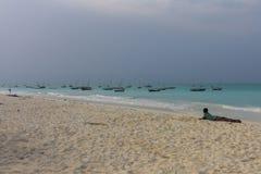 Il ragazzo cerca le barche sulla spiaggia della bianco-sabbia di Nungwi, Zanzibar Fotografia Stock