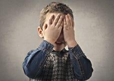 Il ragazzo che dissimula il suo osserva immagini stock libere da diritti