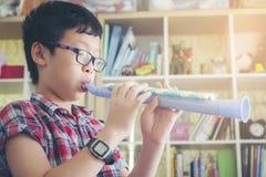 Il ragazzo che gioca il clarinetto, suona la tromba a casa, soffiando una flauto dolce immagine stock libera da diritti