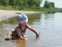 Il ragazzo che gioca nel fiume Fotografia Stock