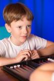 Il ragazzo che gioca un gioco da tavolo ha chiamato Backgammon immagini stock