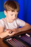 Il ragazzo che gioca un gioco da tavolo ha chiamato Backgammon immagini stock libere da diritti