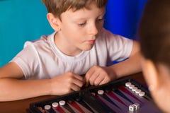 Il ragazzo che gioca un gioco da tavolo ha chiamato Backgammon fotografia stock