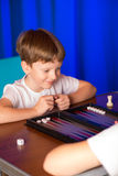 Il ragazzo che gioca un gioco da tavolo ha chiamato Backgammon immagine stock