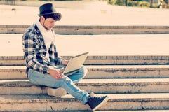 Il ragazzo che lavora al suo computer portatile con un filtro si è applicato nel porcile del instagram Immagini Stock Libere da Diritti