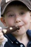 Il ragazzo che mangia il cioccolato congelato ha coperto la banana Fotografie Stock Libere da Diritti