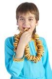 Il ragazzo che mangia un anello del pane sopra bianco immagine stock