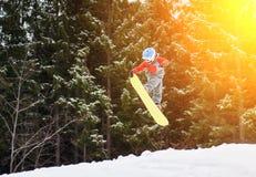 Il ragazzo che salta e tiene una mano sullo snowboard Fotografia Stock Libera da Diritti