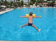 Il ragazzo che salta nella piscina Immagine Stock