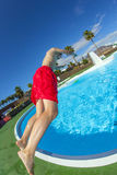 Il ragazzo che salta nello stagno blu Fotografie Stock Libere da Diritti