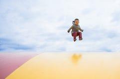 Il ragazzo che salta su su un trampolino all'aperto immagini stock libere da diritti