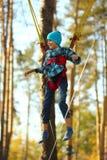 Il ragazzo che salta su un trampolino dell'ammortizzatore ausiliario e che vola nell'aria nel parco di autunno immagine stock libera da diritti