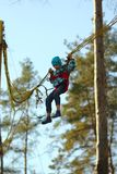 Il ragazzo che salta su un trampolino dell'ammortizzatore ausiliario e che vola nell'aria nel parco di autunno fotografia stock