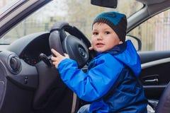 Il ragazzo che si siede dietro la ruota di un'automobile immagine stock libera da diritti