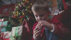 Il ragazzo che si siede sul pavimento vicino ad un albero di Natale ed esamina un regalo archivi video