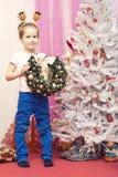 Il ragazzo che si siede sulla sedia rossa con il Natale si avvolge in sue mani fotografie stock