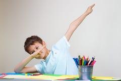 Il ragazzo che si siedono alla tavola e le manifestazioni tamponano il gesto fotografie stock libere da diritti