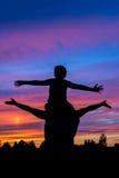Il ragazzo che sta sul padre mette la siluetta sulle spalle con il tramonto variopinto Fotografia Stock