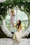 Il ragazzo coglie un fiore per una bella ragazza sui precedenti o Fotografie Stock
