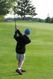 Il ragazzo colpisce la sfera di golf per inverdirsi Fotografia Stock