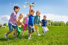 Il ragazzo con altri bambini esegue e tiene il giocattolo dell'aeroplano Fotografia Stock Libera da Diritti