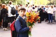 Il ragazzo con i fiori celebra il primo giorno di scuola a Mosca Fotografia Stock