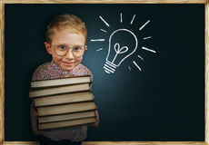 Il ragazzo con i libri si avvicina alla lavagna della scuola Fotografie Stock