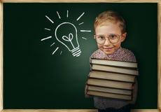 Il ragazzo con i libri si avvicina alla lavagna della scuola Fotografia Stock