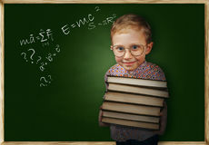 Il ragazzo con i libri si avvicina alla lavagna della scuola Fotografie Stock Libere da Diritti