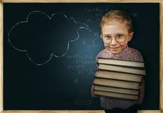 Il ragazzo con i libri si avvicina alla lavagna della scuola Immagini Stock