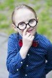 Il ragazzo con il farfallino ed i grandi vetri sta selezionando il suo naso Immagine Stock