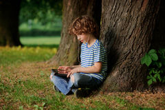 Il ragazzo con la compressa in mani si siede sotto un grande albero Fotografia Stock