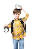 Il ragazzo con la sveglia ed i libri Fotografie Stock Libere da Diritti