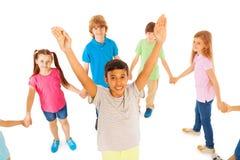 Il ragazzo con le mani sollevate sta nel cerchio degli amici Fotografia Stock