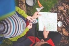 Il ragazzo con suo padre che tiene una bussola e una mappa Immagini Stock