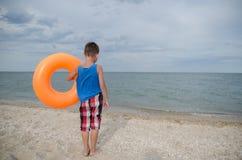 Il ragazzo con un cerchio di nuoto sta sulla riva del mare indietro Fotografia Stock