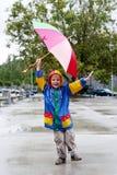 Il ragazzo con un ombrello che si leva in piedi sotto una pioggia Immagini Stock