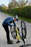 Il ragazzo controlla la sua bici Immagine Stock