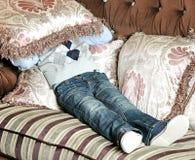 Il ragazzo copre il suo fronte di cuscino Fotografie Stock Libere da Diritti