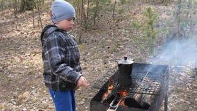 Il ragazzo cucina l'alimento sul fuoco nella griglia Resto del paese video d archivio