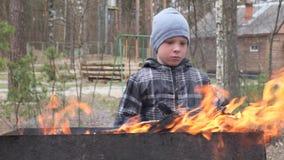 Il ragazzo cucina l'alimento sul fuoco nella griglia Resto del paese archivi video