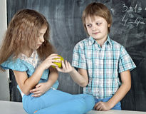 Il ragazzo dà ad una ragazza una mela alla scuola Immagini Stock