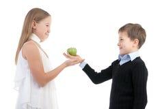 Il ragazzo dà alla ragazza una mela Immagini Stock